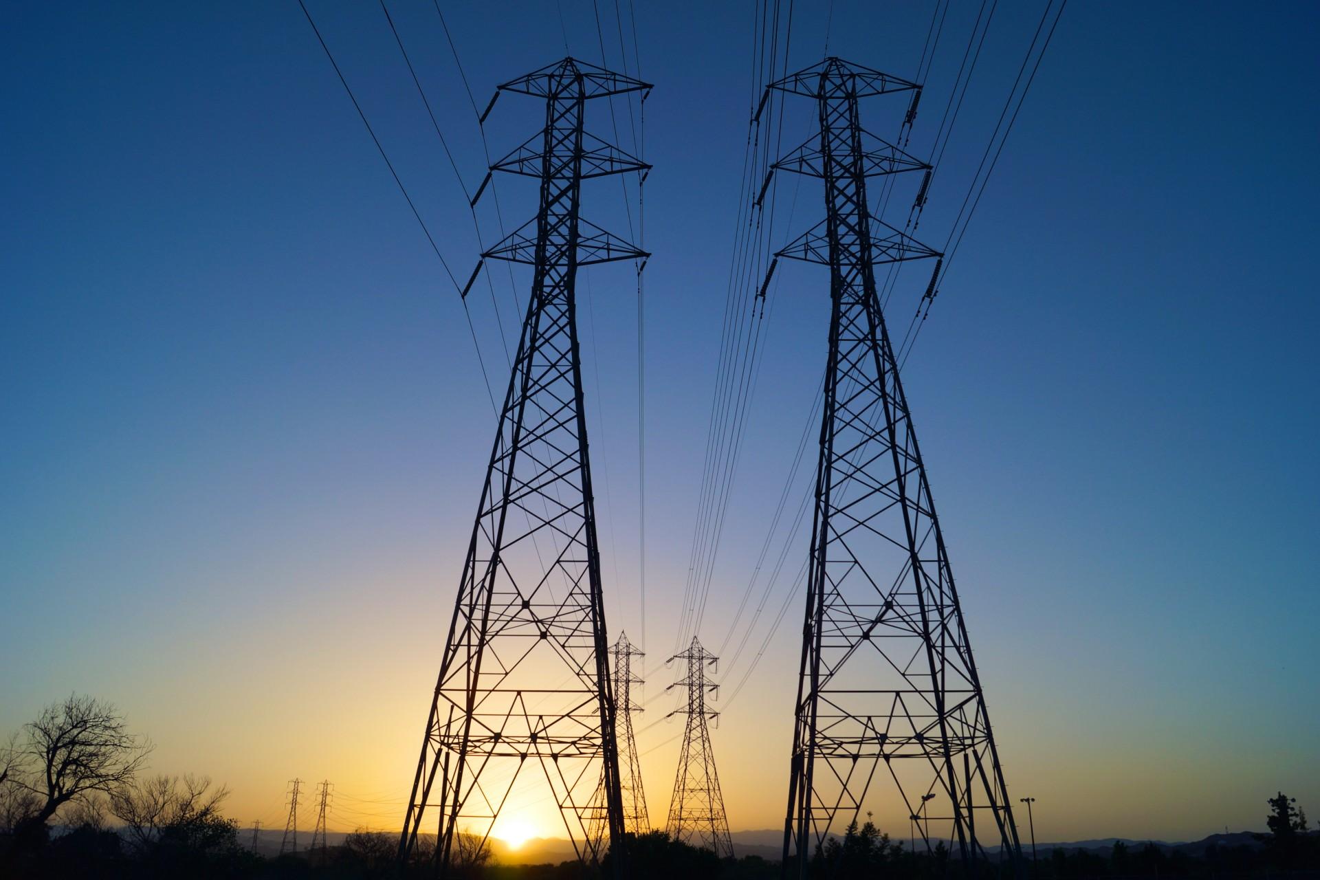 Il sole tramonta dietro a due linee di alimentazione per l'energia elettrica in acciaio in California.