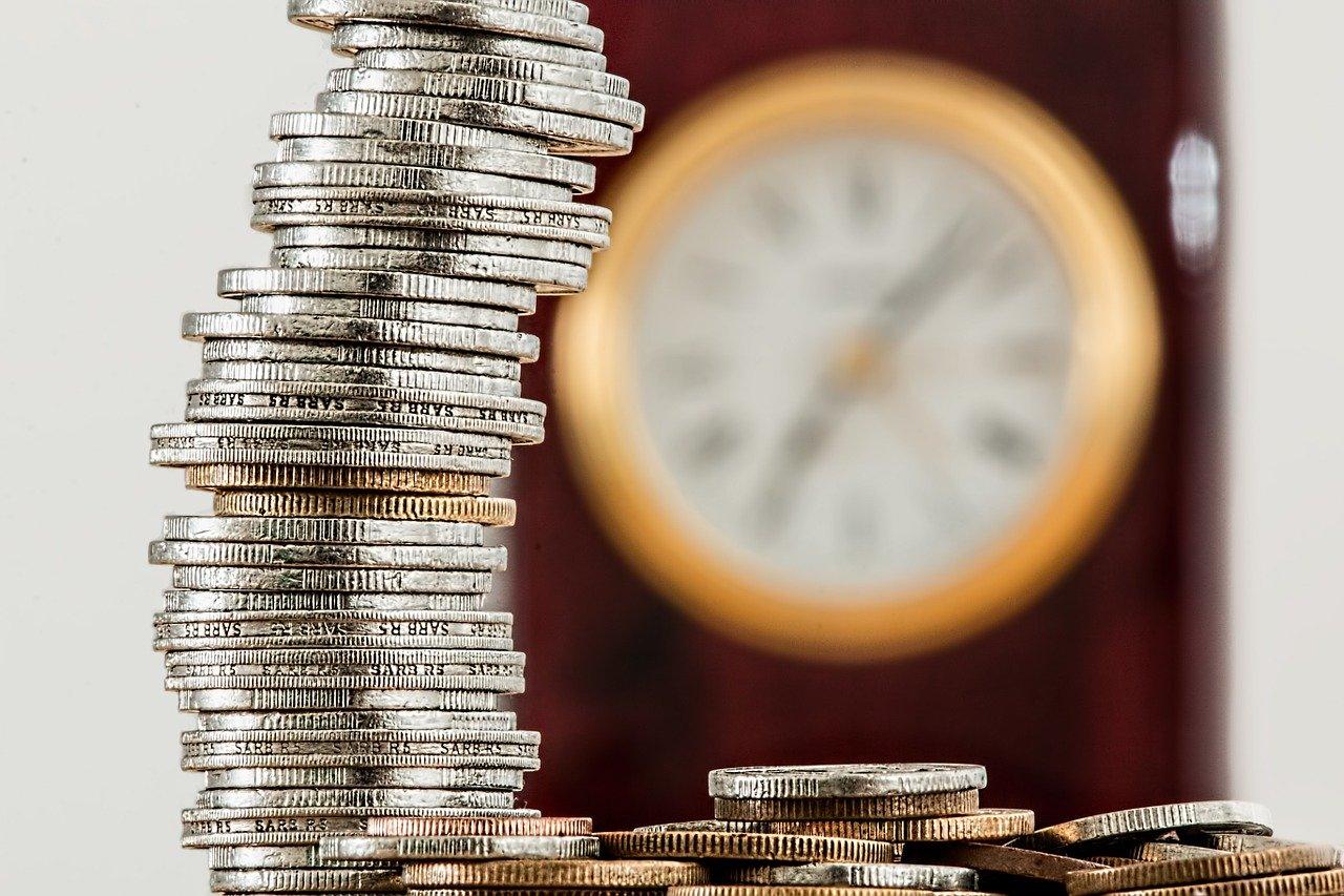 Pila di monete e orologio