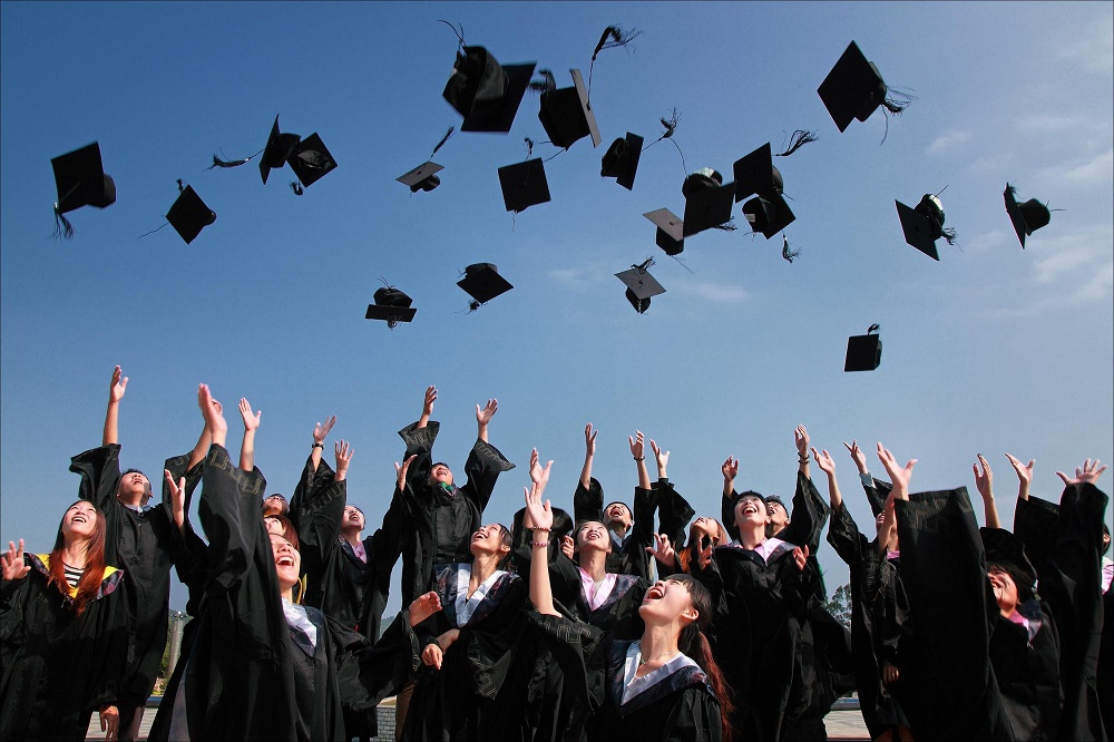 Universitari mentre lanciano in alto il cappello
