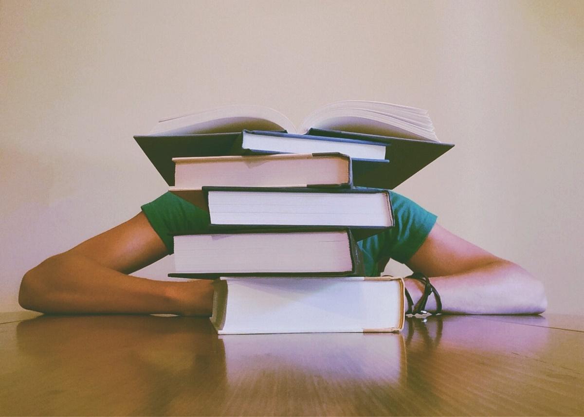Maturità 2020 pila di libri che nascondono il viso di una persona