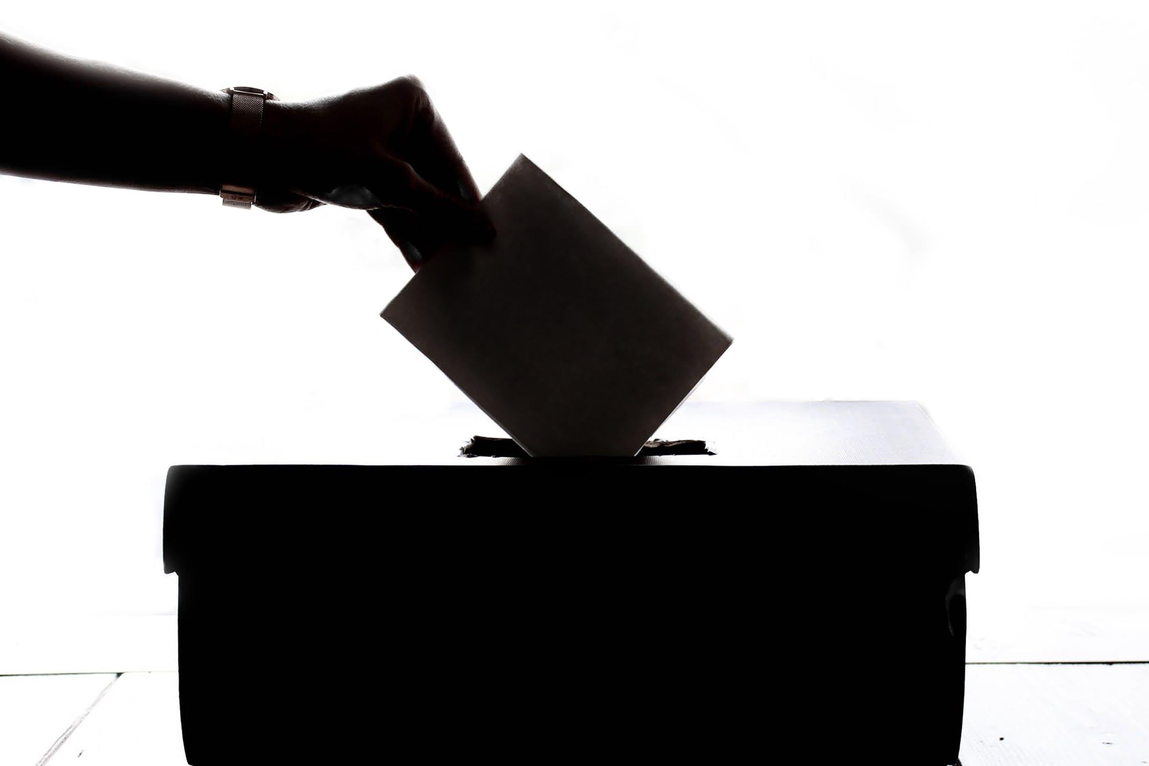 Ombra di una mano che inserisce una scheda in un'urna
