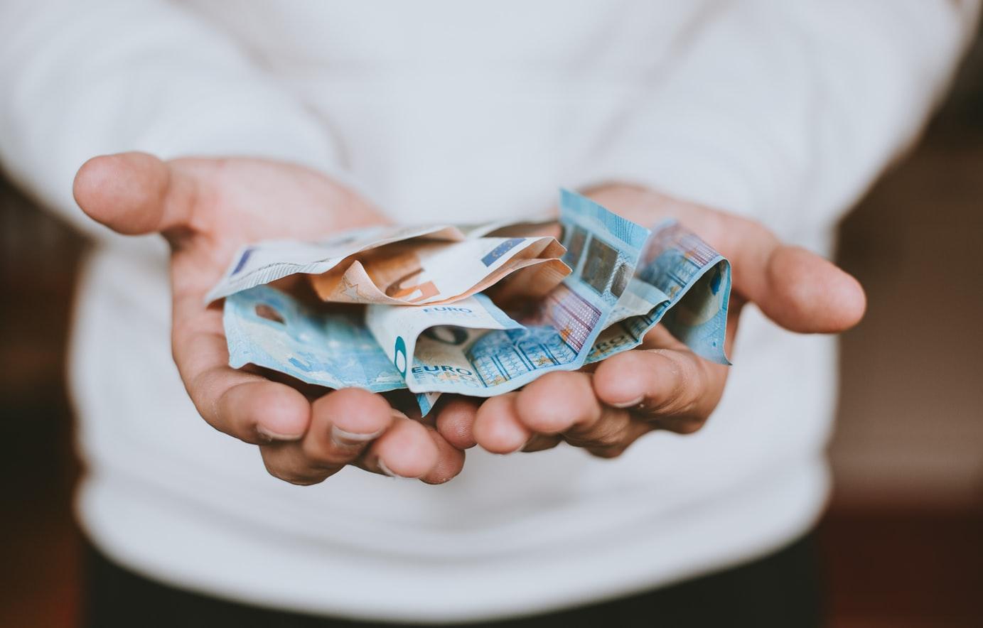 palmi delle mani con delle banconote da 20 e 50 euro