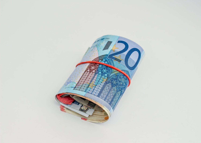 banconote in euro arrotolate in un elastico rosso