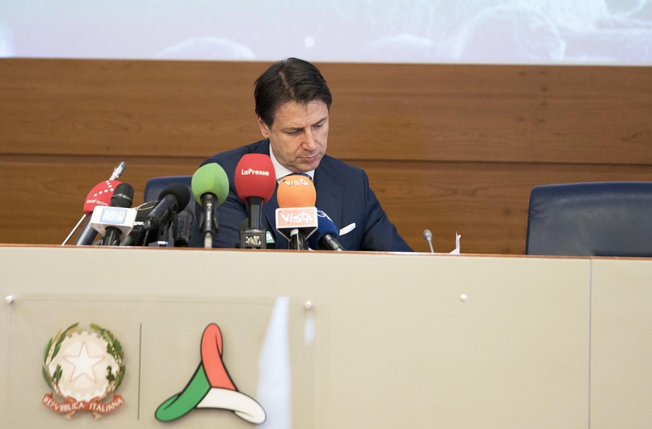 Il presidente del Consiglio Conte seduto durante una conferenza stampa