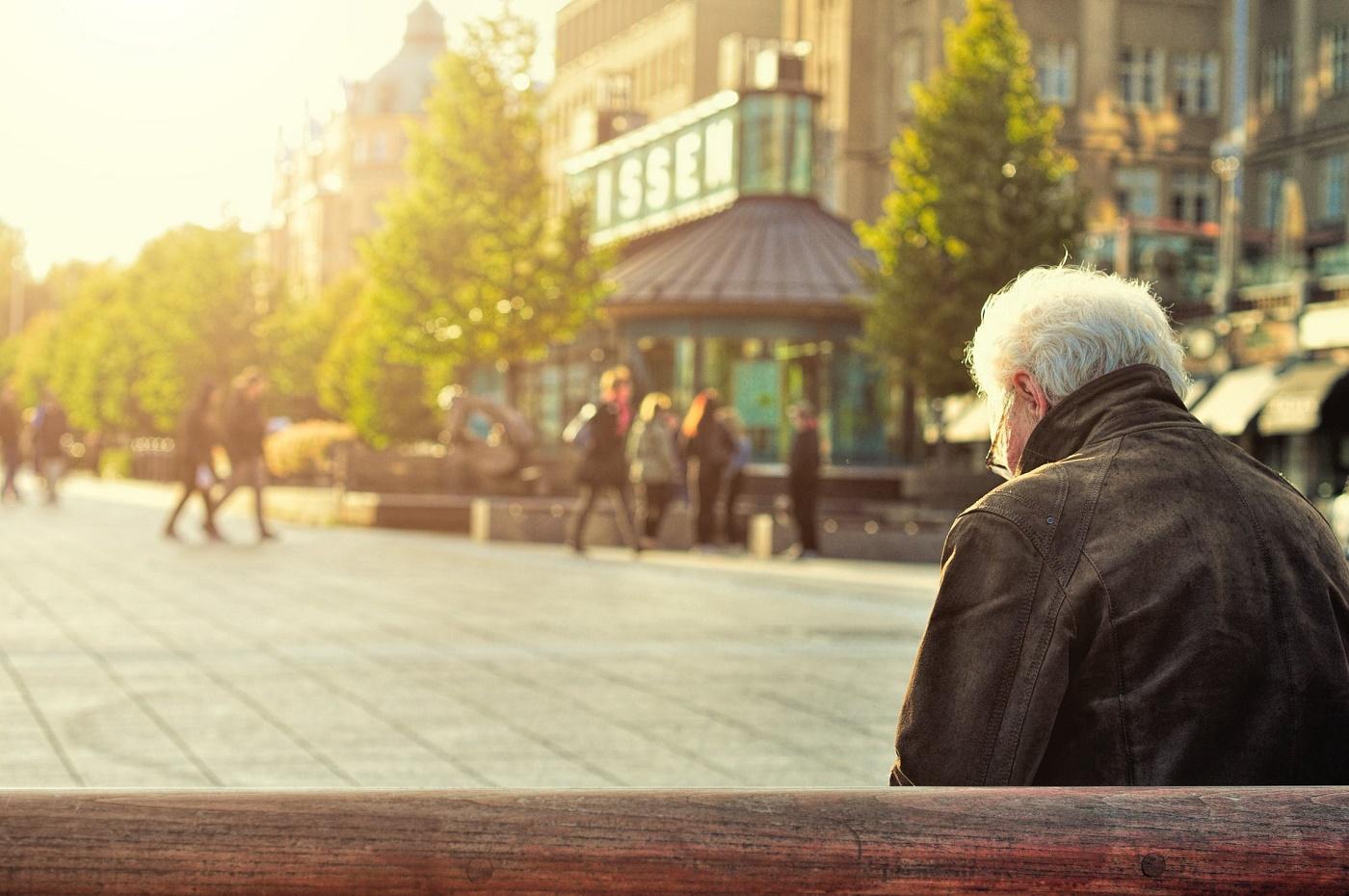 Uomo anziano fotografato di spalle su una panchina