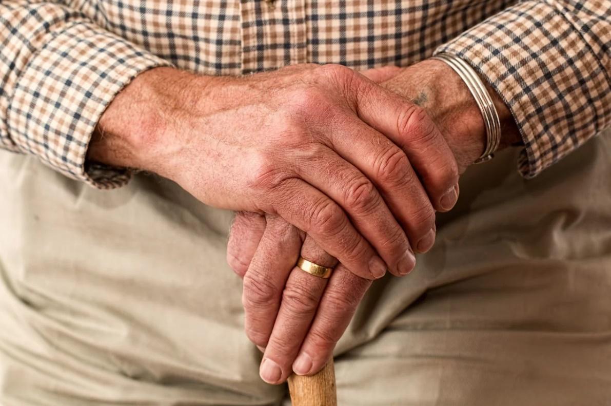 Mani di un anziano una sull'altra con bastone ed anello