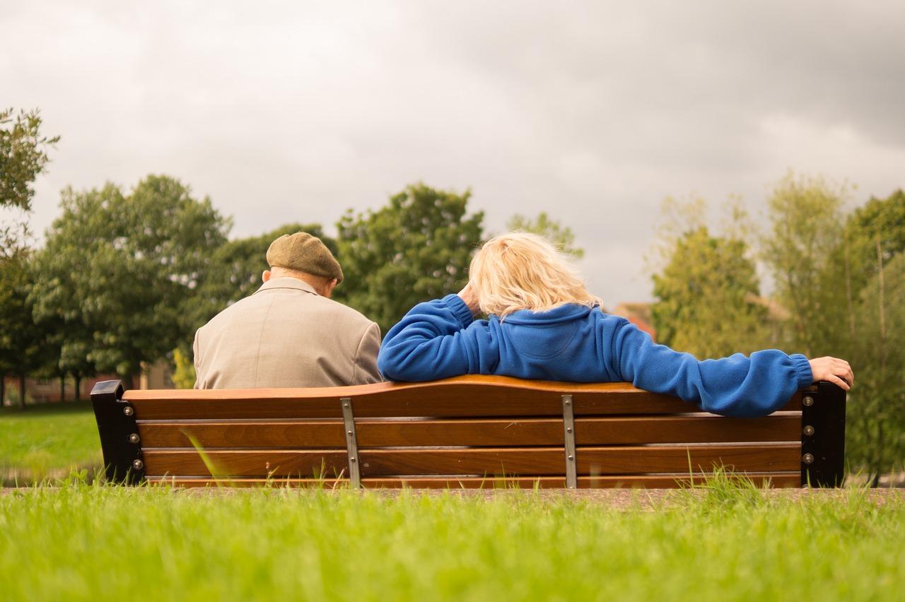 Coppia di persone anziane di spalle sedute su una panchina
