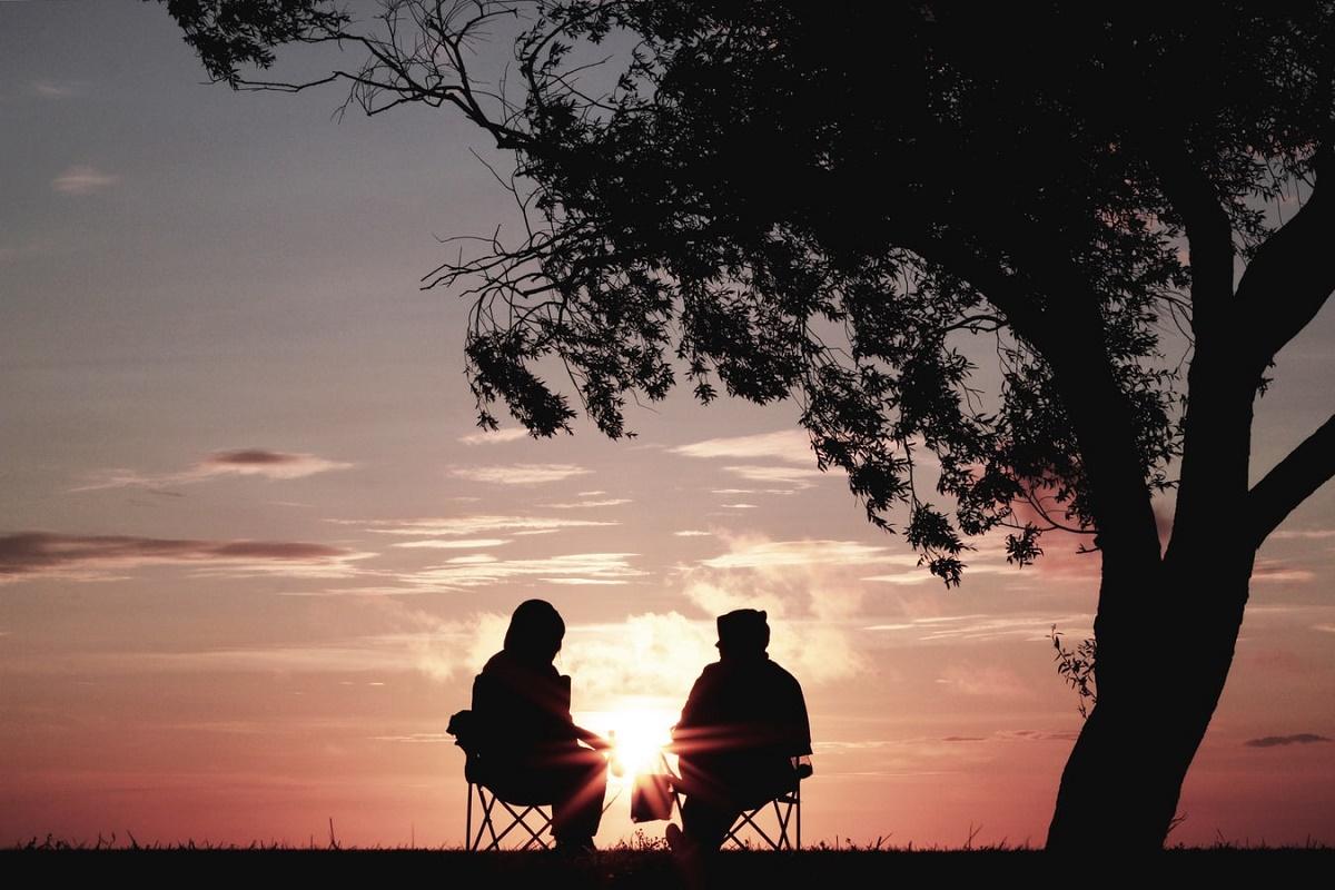 Due persone di spalle sotto un albero con di fronte il tramonto