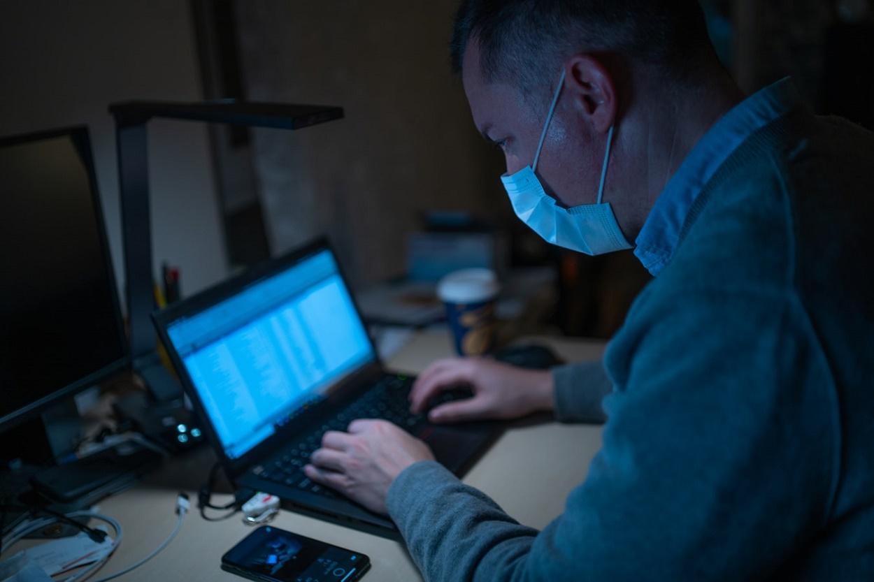 Uomo al computer con la mascherina protettiva