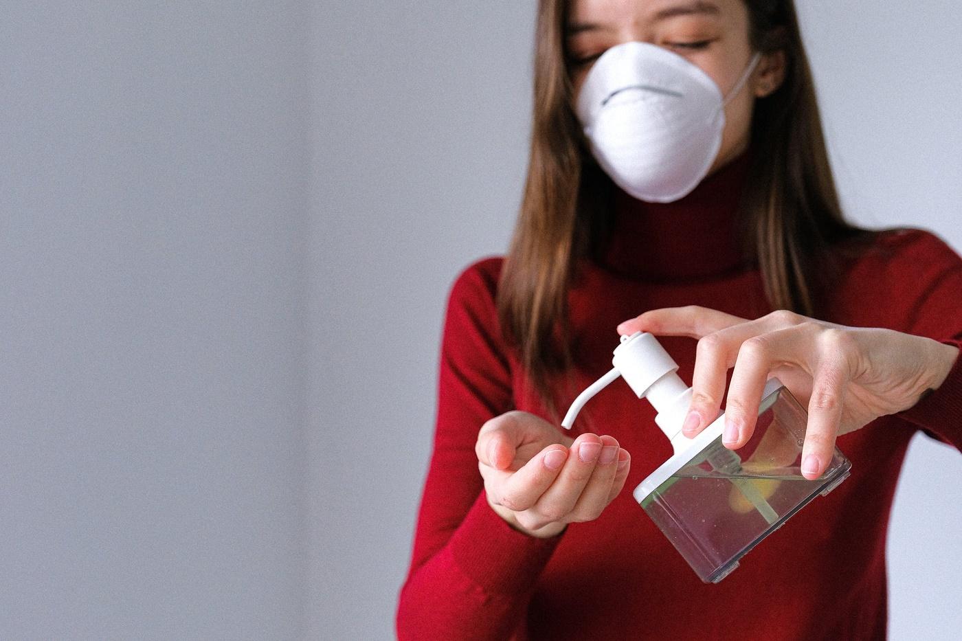 Ragazza con mascherina mentre si deterge le mani
