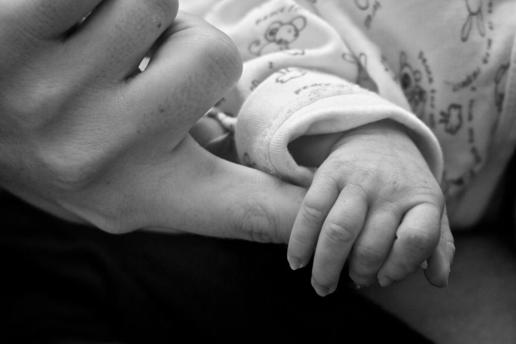 Mano di bambina tiene per mano il mignolo di un adulto