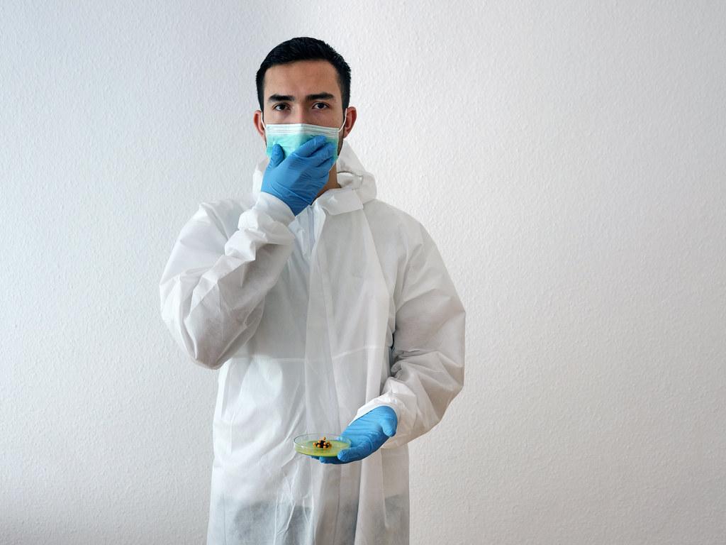 Uomo con camice, mascherina e guanti