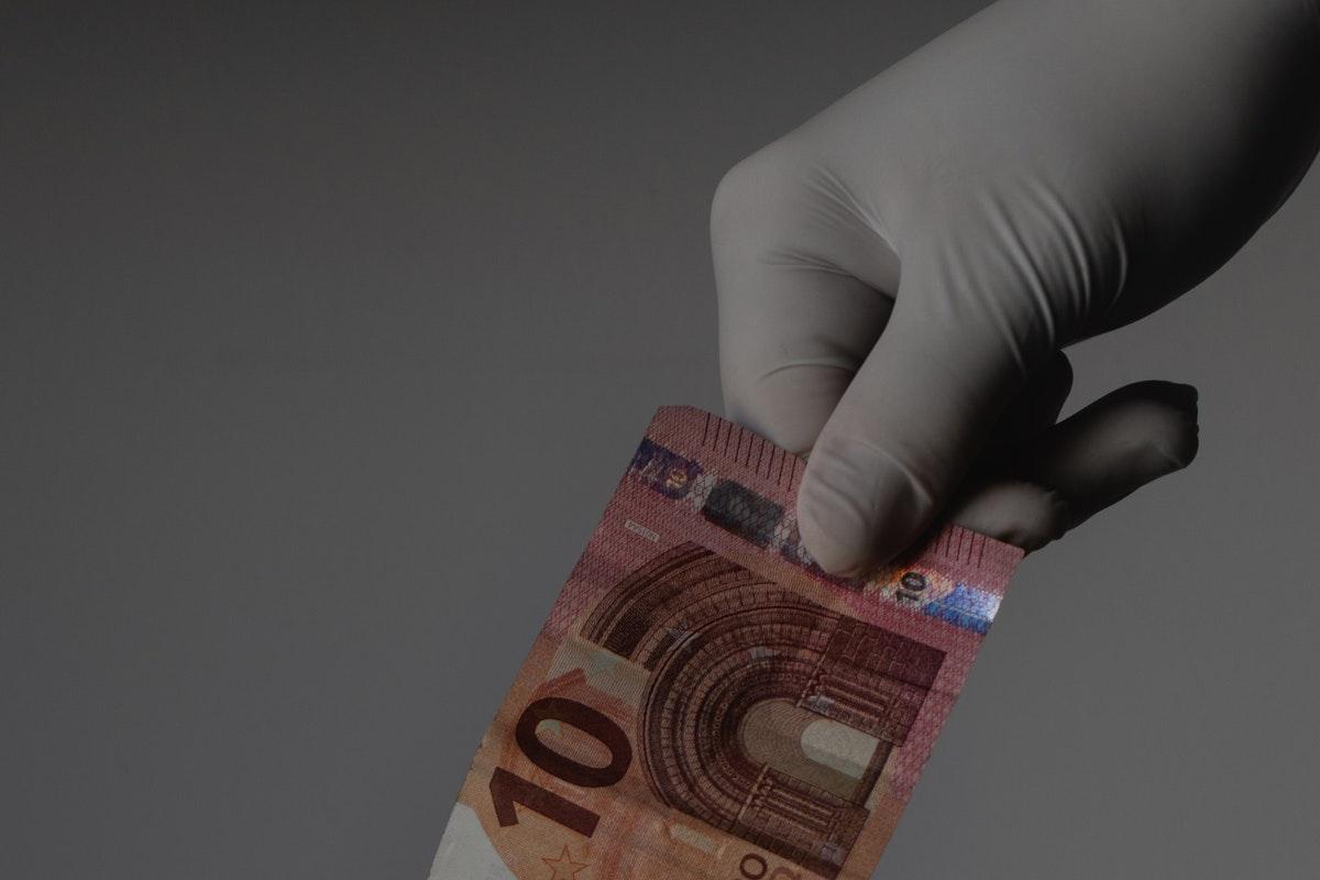 una mano che indossa un guanto in lattice tiene una banconota da 10 euro