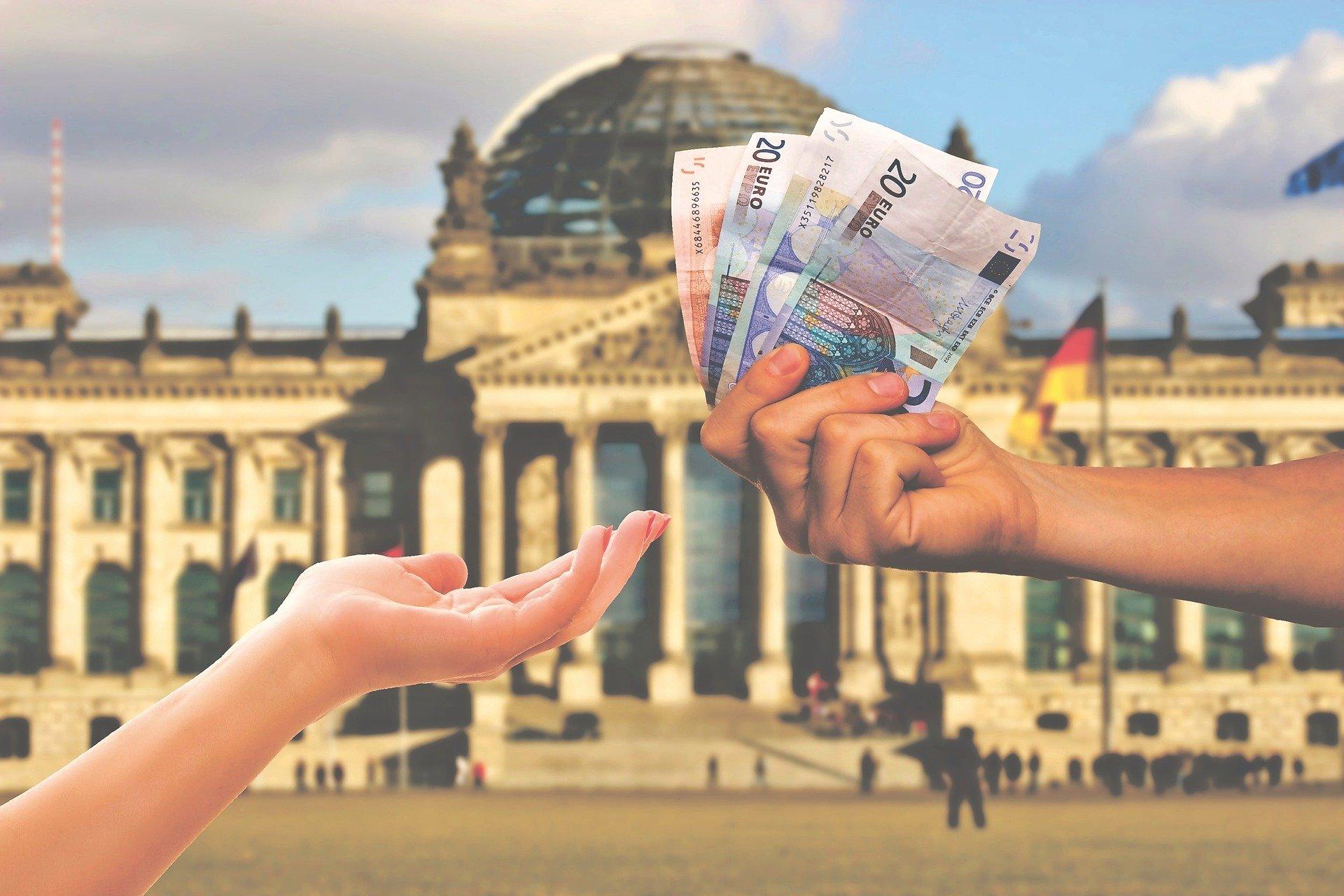 consegna a mano di banconote di euro con lo sfondo di Berlino