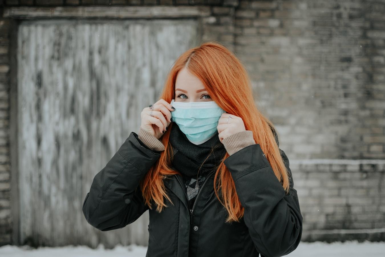 Donna coi capelli rossi mentre indossa una mascherina