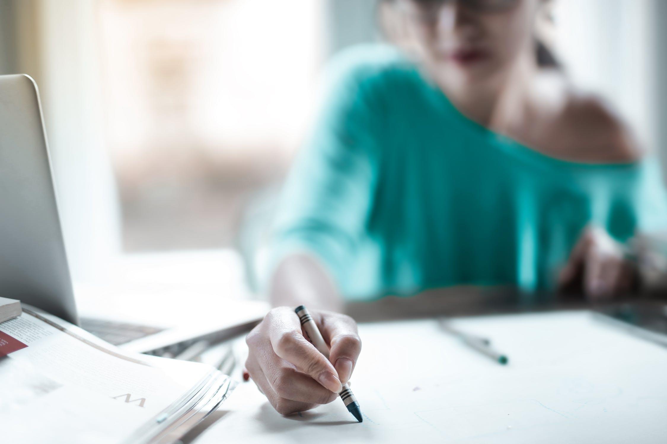 Donna al pc con penna tra le mani