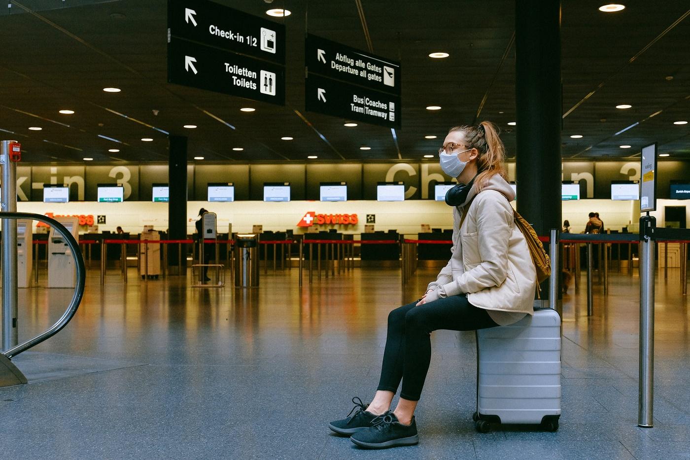 Donna con mascherina seduta su un trolley all'interno di un aeroporto vuoto
