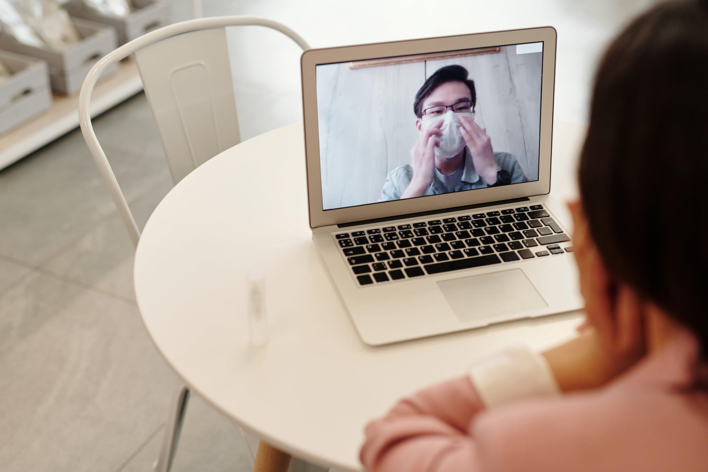Due persone che dialogano in video tramite il pc. Una persona di spalle e l'altra in video con la mascherina