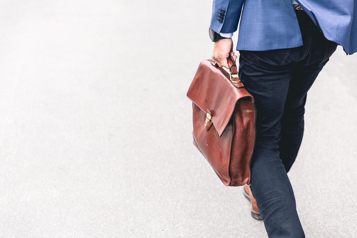 Uomo di spalle con in mano un piccola valigia marrone