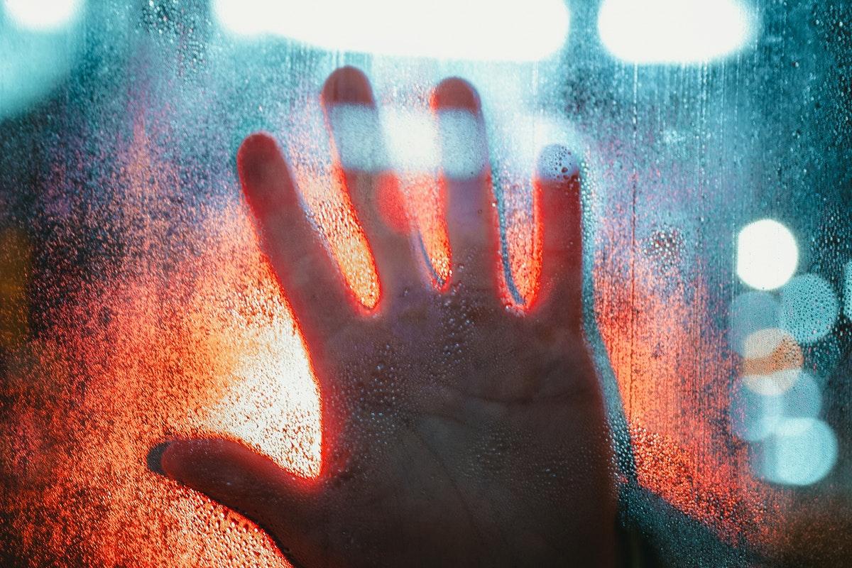 mano che tocca una porta di vetro
