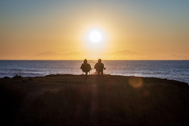 Due persone sedute ritratte di spalle e di fronte al sole