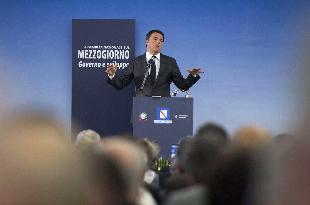 Matteo Renzi durante un evento pubblico in piedi e con le braccia allargate