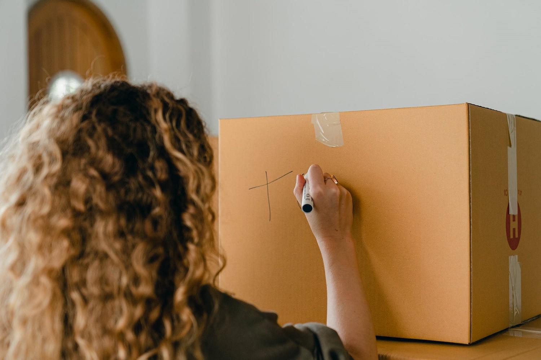 Donna riccia di spalle con pennarello mentre scrive su un cartone