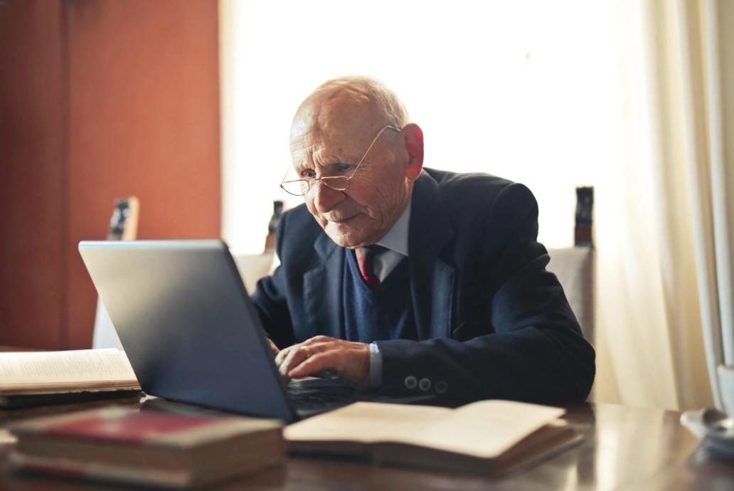 Uomo anziano seduto alla scrivania davanti a pc portatile